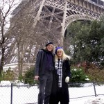 Liz & Doc modeling the berets in the shadow of the Eiffel Tower.